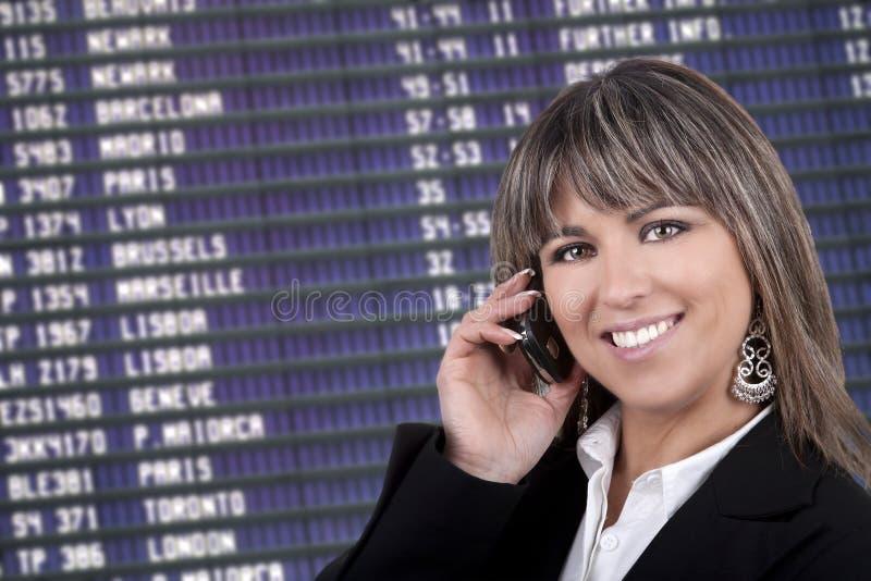 Geschäftsfrau mit Handy im Flughafen stockbild