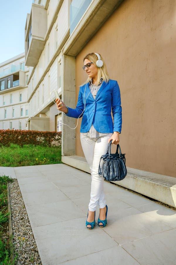 Geschäftsfrau mit Kopfhörern und Mobile lizenzfreie stockfotos