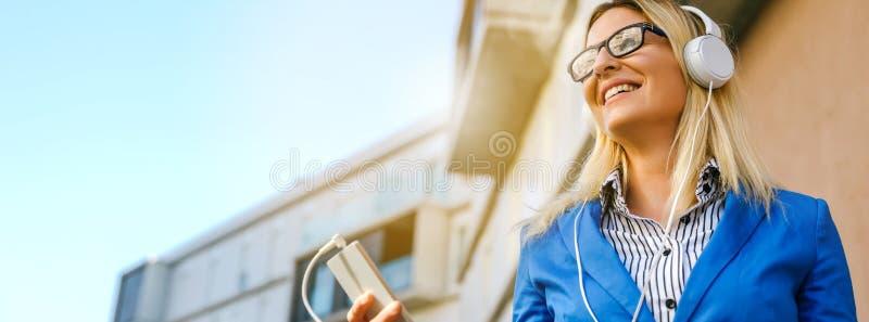 Geschäftsfrau mit Kopfhörern und Mobile stockbilder