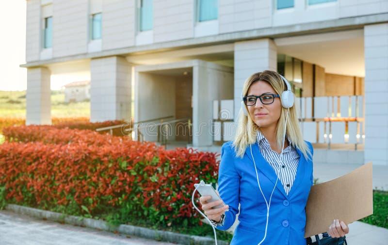 Geschäftsfrau mit Kopfhörern und Mobile lizenzfreies stockfoto