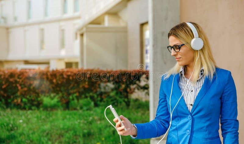 Geschäftsfrau mit Kopfhörern und Mobile lizenzfreie stockfotografie