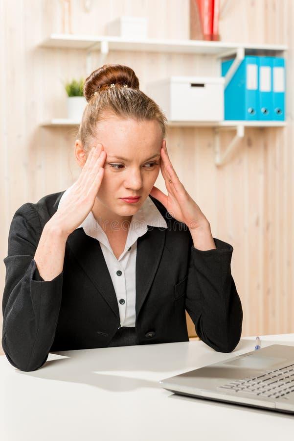 Geschäftsfrau mit Kopfschmerzen, die den Laptop betrachten stockfotografie