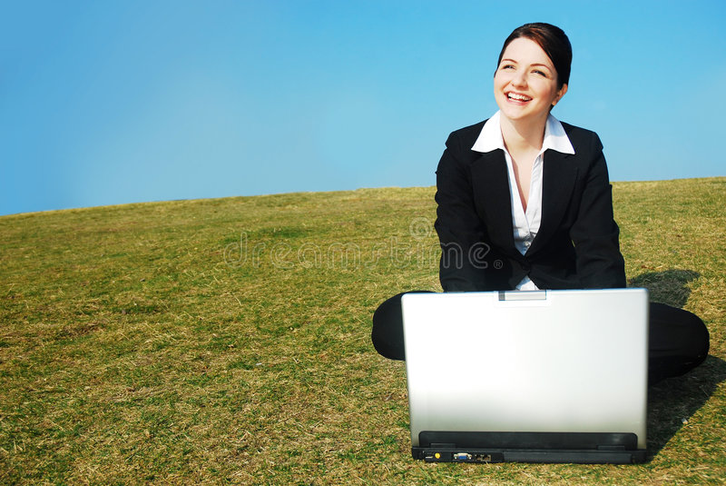 Geschäftsfrau mit Laptop auf dem Gebiet stockbild