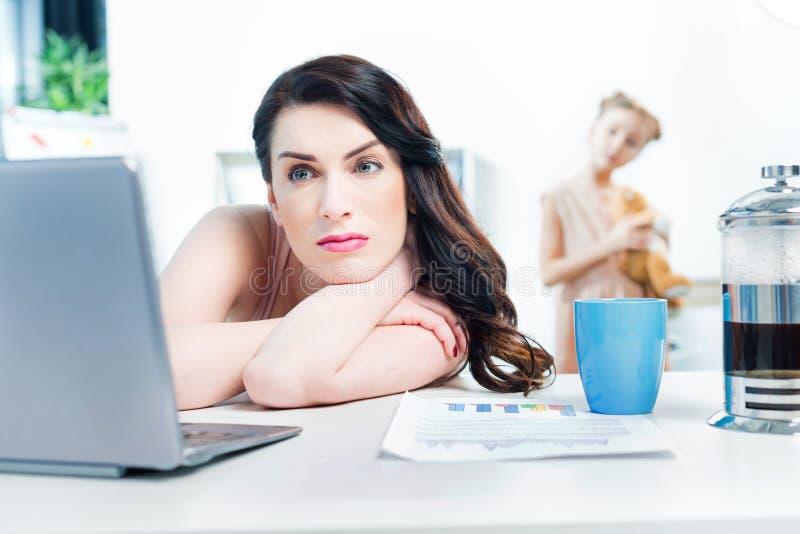 Geschäftsfrau mit Laptop und Kaffeetasse im Büro mit Tochter hinten lizenzfreie stockfotografie