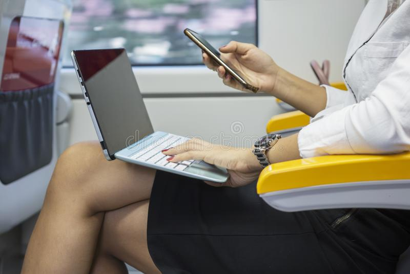 Geschäftsfrau mit Laptop und Telefon im Zug stockbilder