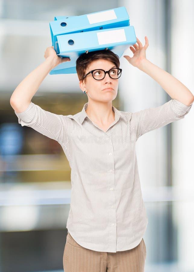 Geschäftsfrau mit Ordnern auf ihrem Kopf, der eine Balance hält lizenzfreie stockbilder