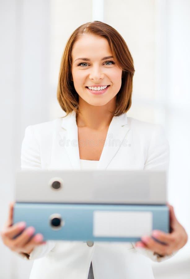 Geschäftsfrau mit Ordnern im Büro lizenzfreie stockfotografie