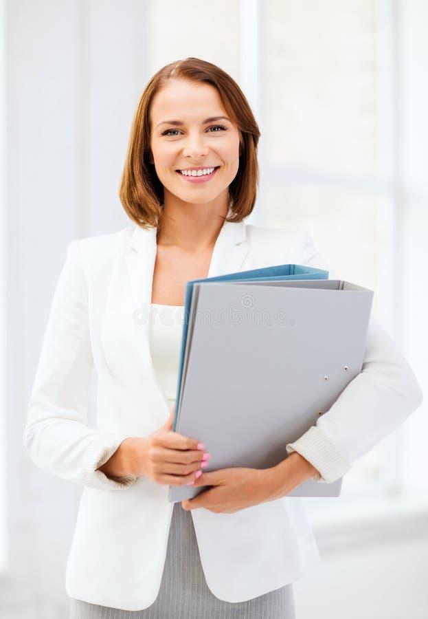Geschäftsfrau mit Ordnern im Büro lizenzfreie stockfotos