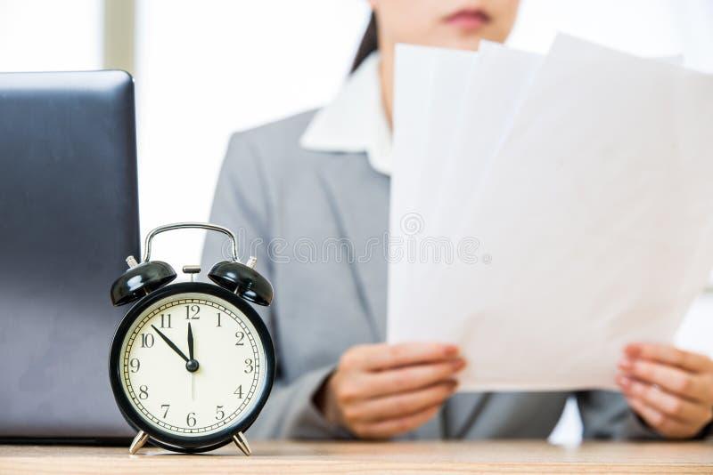 Geschäftsfrau mit Papieren über Tabelle mit Weckerlaptop lizenzfreie stockfotos