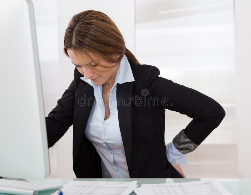 Geschäftsfrau mit Rückenschmerzen stockfoto