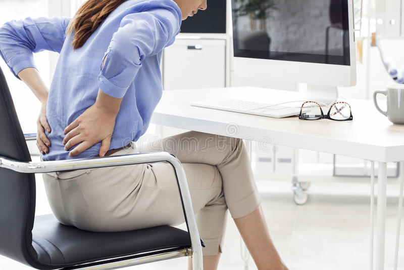 Geschäftsfrau mit Rückenschmerzen im Büro lizenzfreie stockfotos