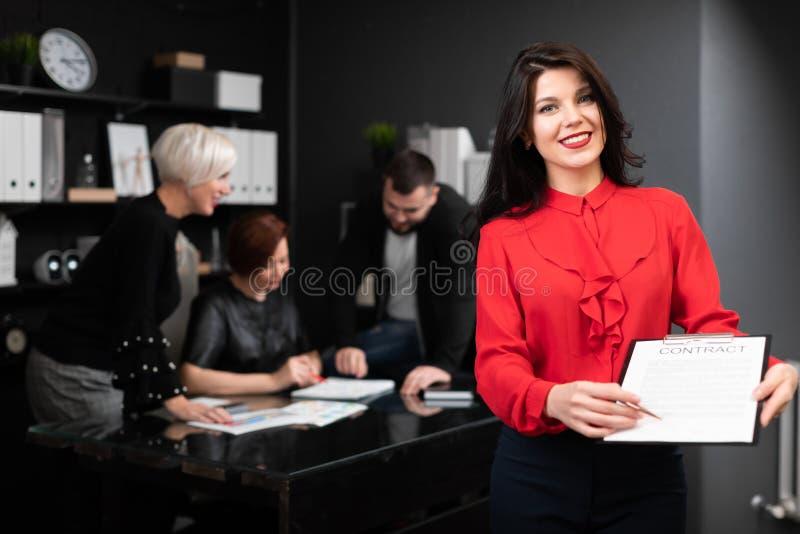 Geschäftsfrau mit Stift und Vertrag auf Hintergrund von Büroangestellten das Projekt besprechen lizenzfreies stockbild