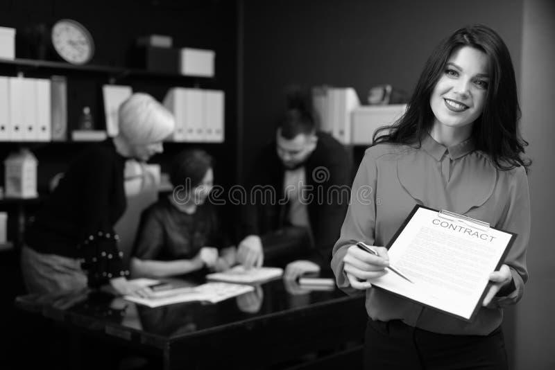 Geschäftsfrau mit Stift und Vertrag auf Hintergrund von Büroangestellten das Projekt besprechen lizenzfreie stockfotografie