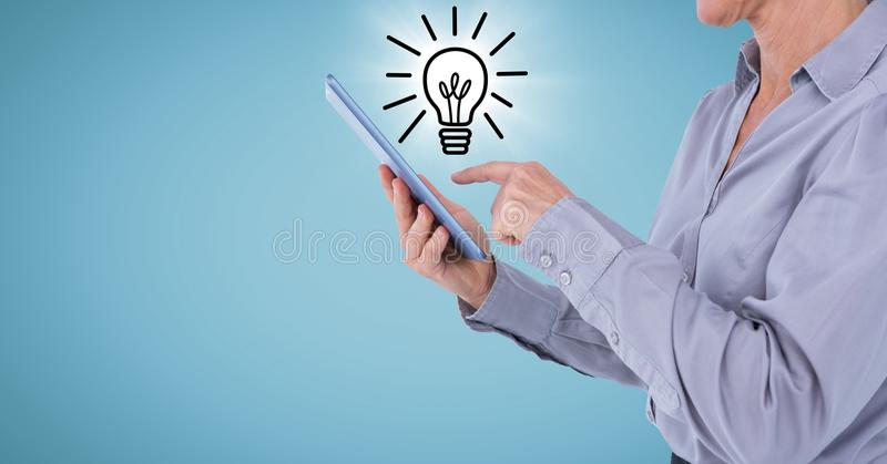 Geschäftsfrau mit Tablette und Glühlampe kritzeln mit Aufflackern gegen blauen Hintergrund stockbild