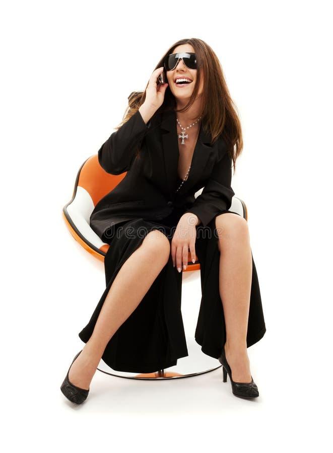 Geschäftsfrau mit Telefon im orange Stuhl stockfoto