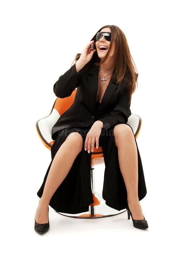 Geschäftsfrau mit Telefon im orange Stuhl lizenzfreies stockbild