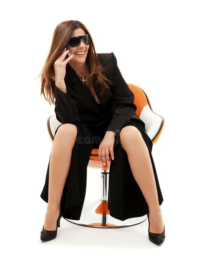 Geschäftsfrau mit Telefon im orange Stuhl stockfotos