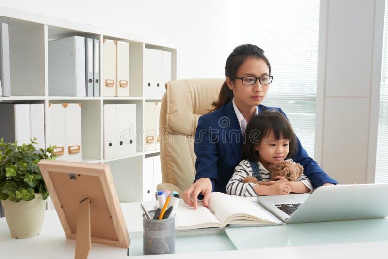 Geschäftsfrau mit Tochter bei der Arbeit lizenzfreie stockfotos