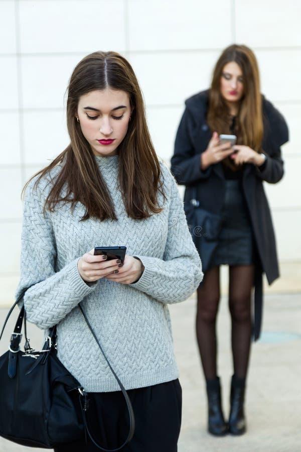 Geschäftsfrau mit zwei Jungen, die Handy in der Straße verwendet stockbilder