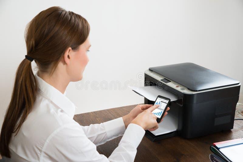 Geschäftsfrau With Mobile Phone angeschlossen an Drucker stockfoto