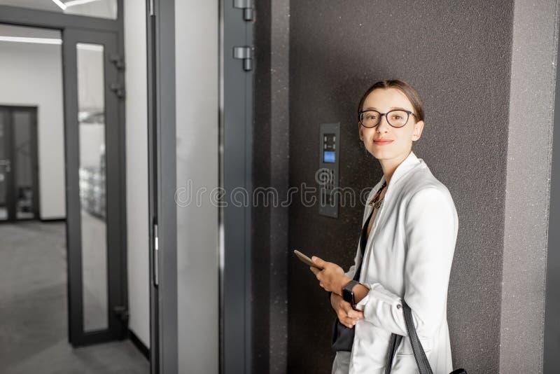 Geschäftsfrau nahe dem errichtenden Eingang stockfoto