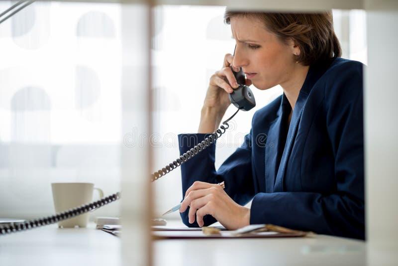 Geschäftsfrau oder Direktorin, die an einem Überlandleitungstelefon sprechen lizenzfreies stockbild