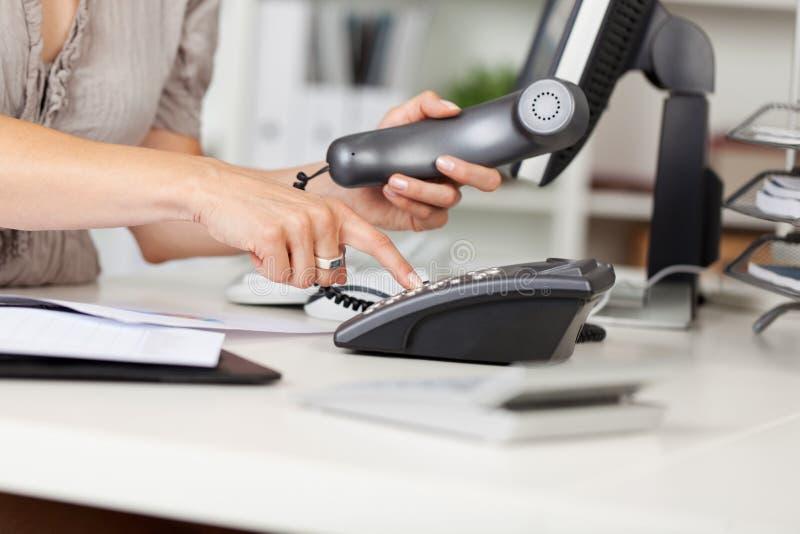 Geschäftsfrau Pressing Number Button am Schreibtisch lizenzfreie stockbilder