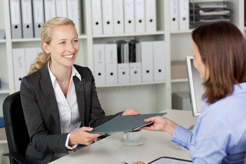 Geschäftsfrau Receiving Application File vom Kandidaten stockfotos