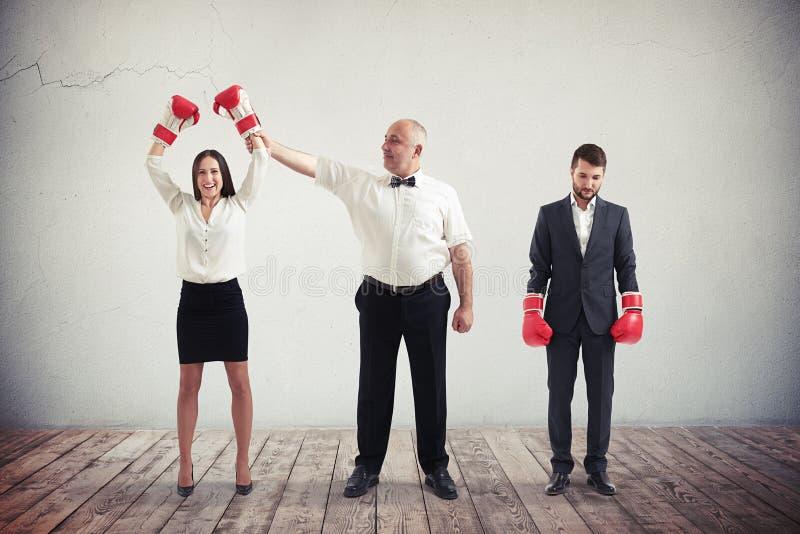 Geschäftsfrau schlägt den Geschäftsmann in der Boxveranstaltung stockbilder