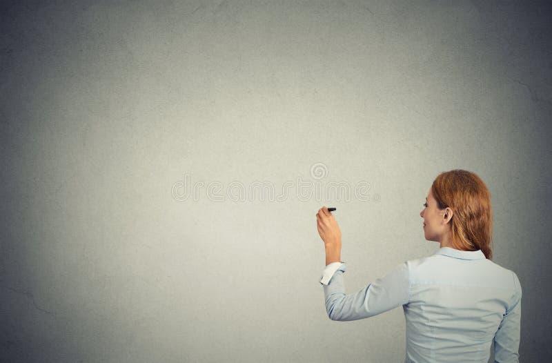 Geschäftsfrau schoss von hinten Schreiben auf Wand lizenzfreie stockfotos