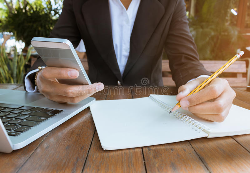 Geschäftsfrau schreiben auf Notizbuch und verwenden das Handyarbeiten im Freien im Kaffeestubeweinleseton lizenzfreie stockfotografie
