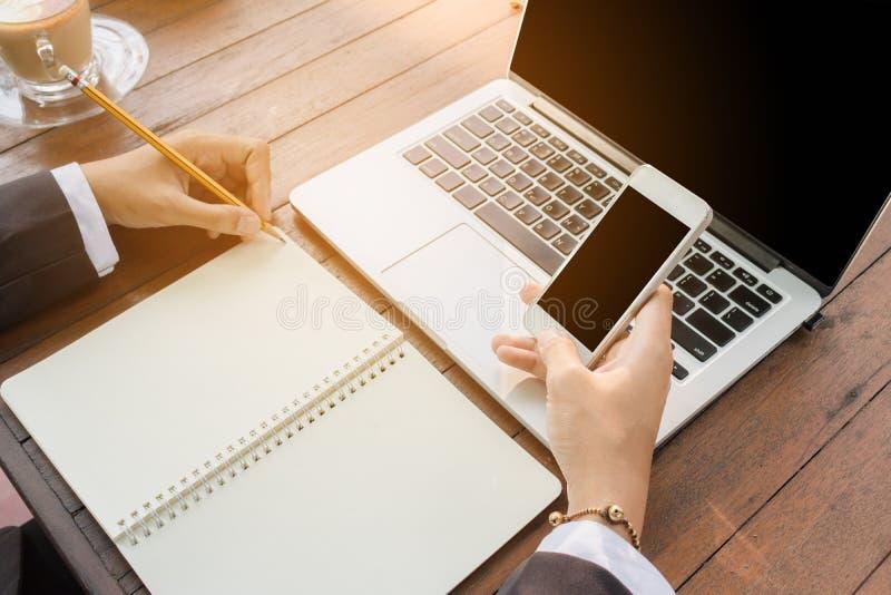 Geschäftsfrau schreiben auf Notizbuch und verwenden das Telefonarbeiten im Freien im Kaffeestubeweinleseton lizenzfreie stockfotos