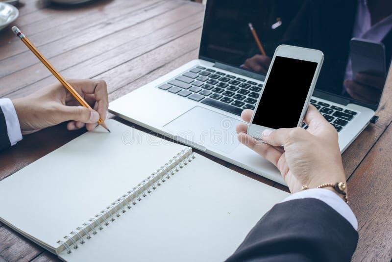 Geschäftsfrau schreiben auf Notizbuch und verwenden Telefonfunktion lizenzfreies stockfoto