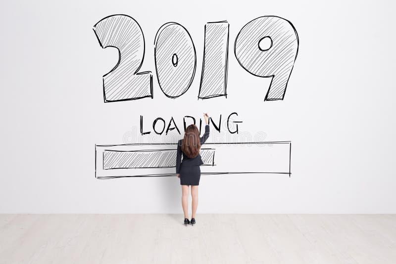Geschäftsfrau schreiben 2019 Text auf weißen Wandhintergrund lizenzfreies stockbild