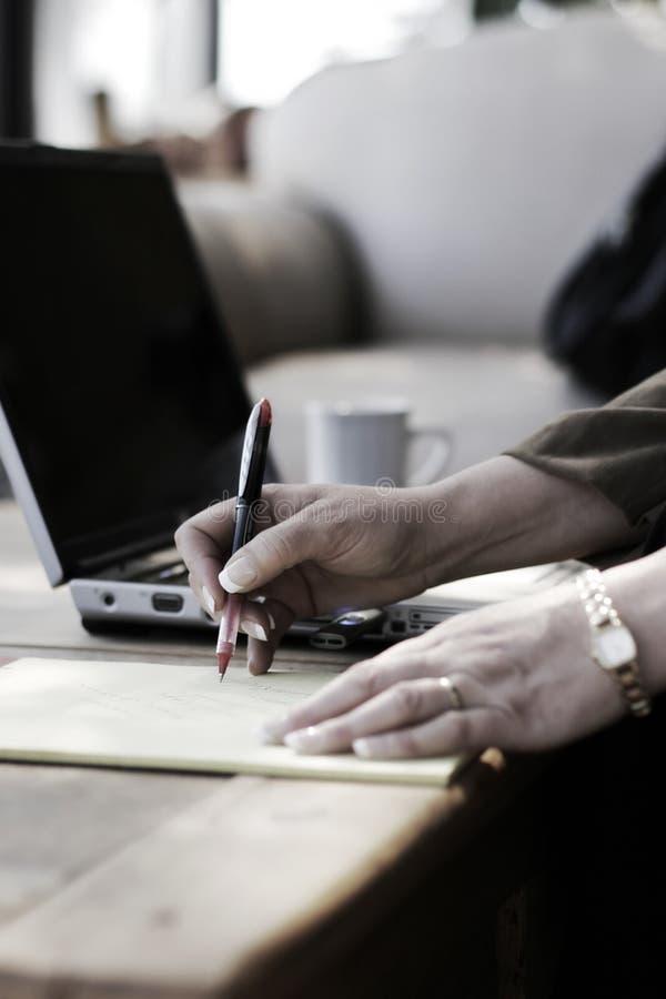 Geschäftsfrau-Schreibens-Anmerkungen im Hotel-Atrium lizenzfreies stockbild