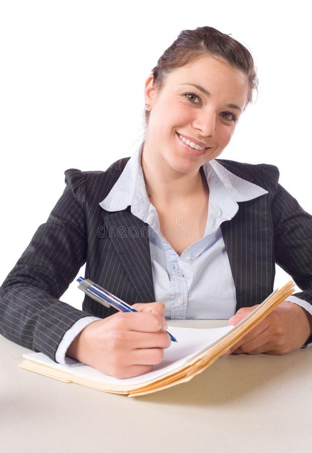 Geschäftsfrau-Schreibensanmerkungen am Schreibtisch lizenzfreie stockfotos