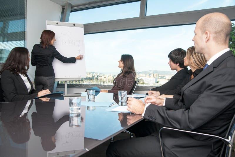 Geschäftsfrau schreibt auf Flip-Chart stockfoto