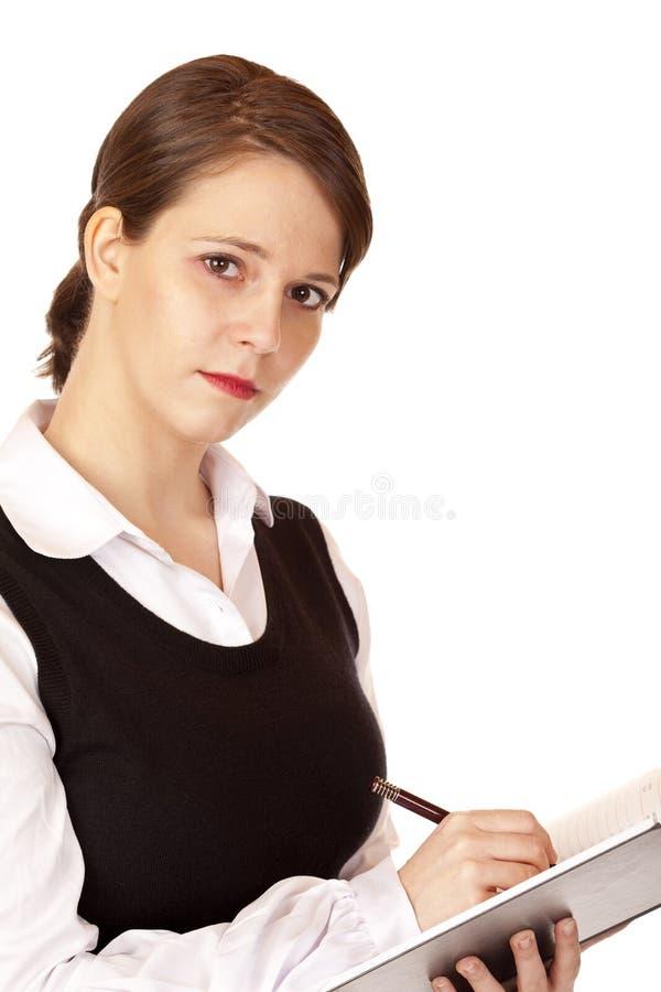 Geschäftsfrau schreibt in Notizblock lizenzfreie stockfotografie
