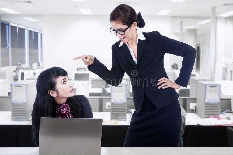 Geschäftsfrau, die am Angestellten schreit stockbild