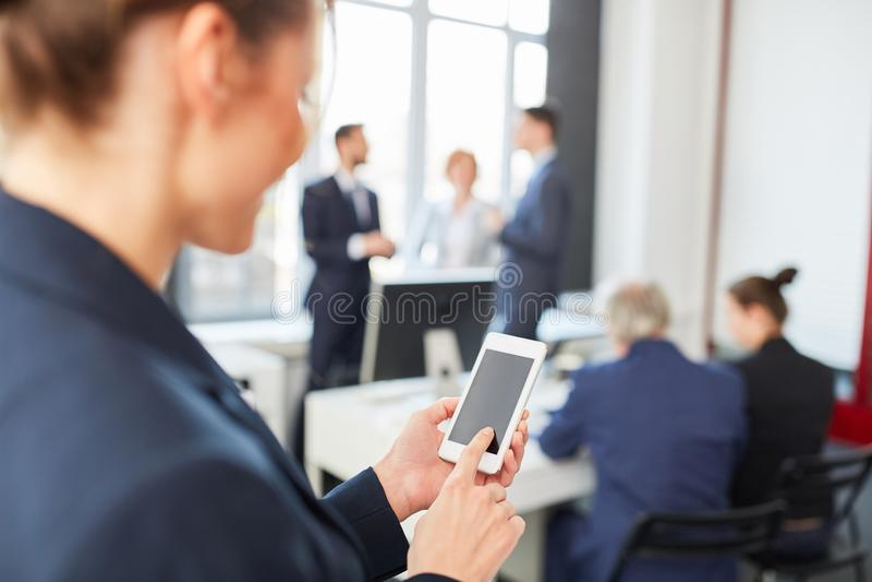 Geschäftsfrau sendet SMS mit Smartphone lizenzfreie stockbilder