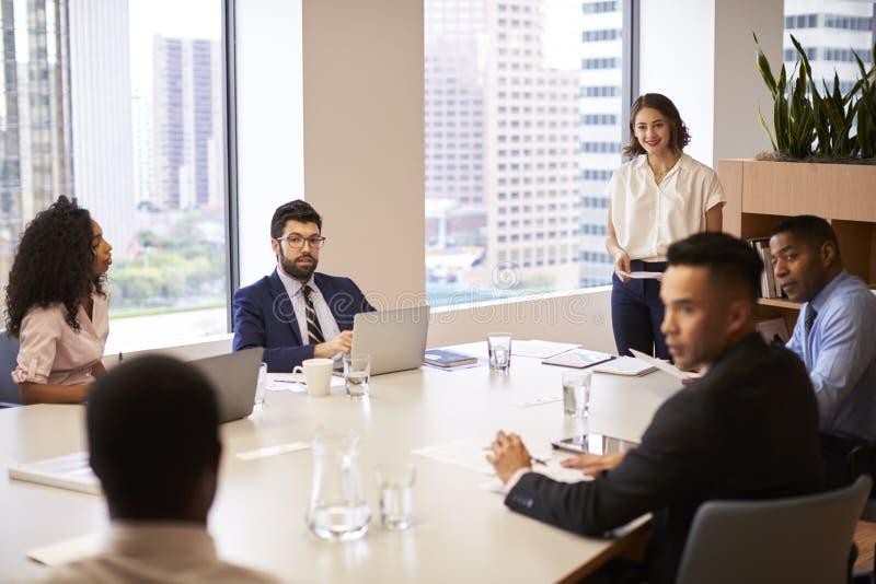 Geschäftsfrau Standing Giving Presentation zu den Kollegen im modernen Bürogroßraum lizenzfreie stockbilder