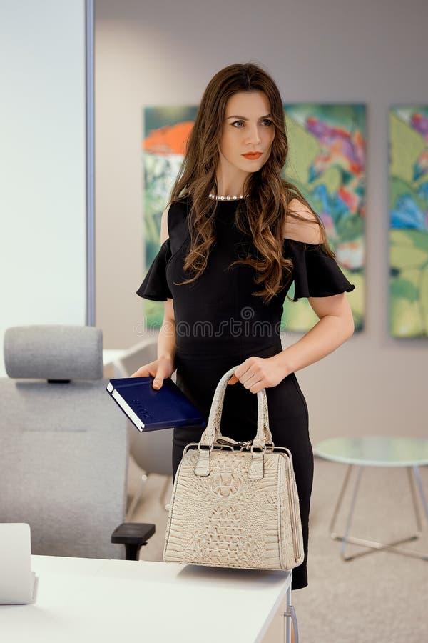 Geschäftsfrau steht mit einer Tasche in seiner Hand lizenzfreie stockfotos