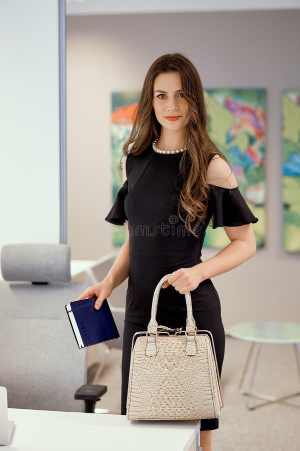 Geschäftsfrau steht mit einer Tasche in seiner Hand lizenzfreies stockbild