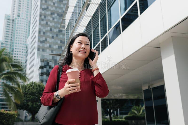 Geschäftsfrau-Talking On Cell-Telefon und Austauschen stockbild