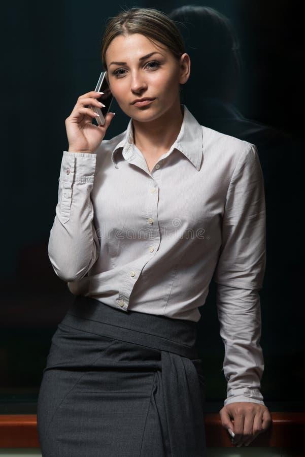 Geschäftsfrau Talking On Telefone im Büro stockbild