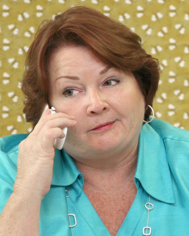 Geschäftsfrau am Telefon an ihrem Schreibtisch stockfotografie