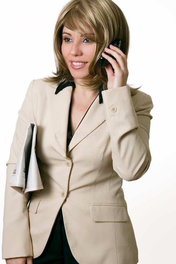 Geschäftsfrau am Telefon mit Zeitung unter Arm lizenzfreie stockfotografie