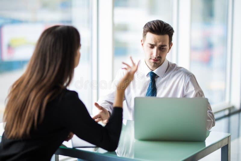 Geschäftsfrau und Geschäftsmann, die bei der Arbeit beim Arbeiten an neuem Projekt auf Laptop sprechen lizenzfreie stockbilder