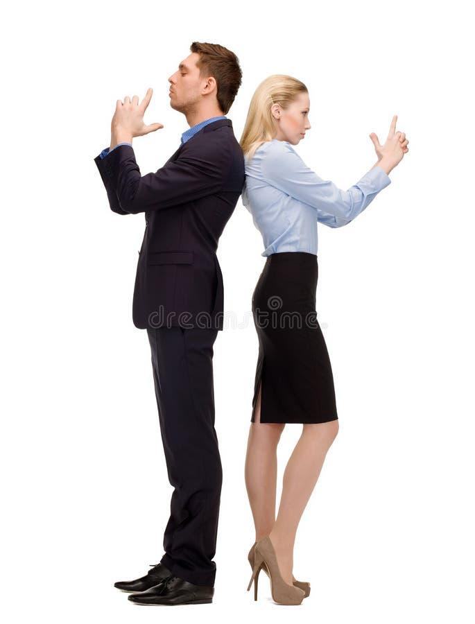Geschäftsfrau und Geschäftsmann mit eingebildeten Gewehren lizenzfreie stockbilder