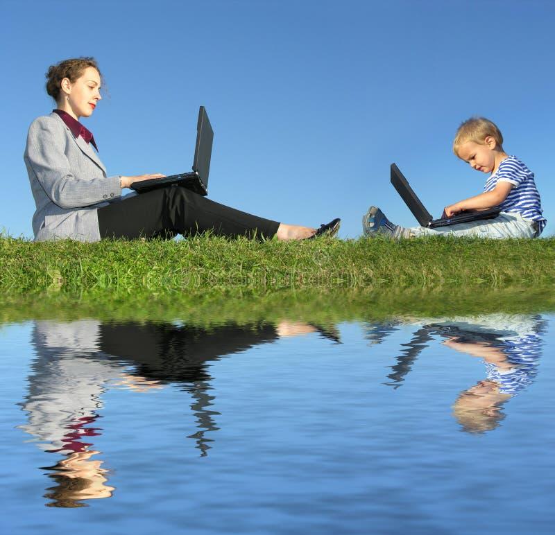 Geschäftsfrau und Kind sitzen mit Notizbüchern stockbild